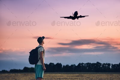 Traveler is looking at the landing airplane