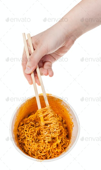 hand keeps chopsticks in cooked instant noodles