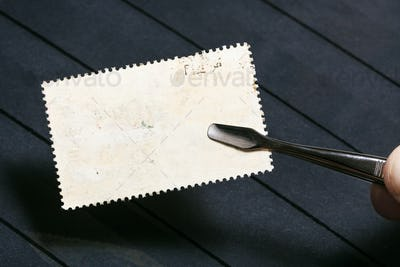 tongs keeps postage stamp with unused back side