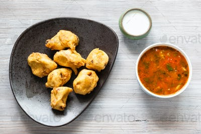 Chicken Pakoda pieces on plate on wooden board