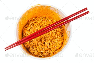 red chopsticks over cup with spicy instant noodles