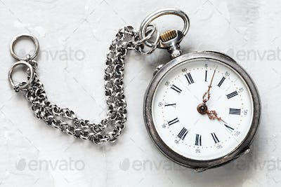 retro pocket watch with chain on white plaster