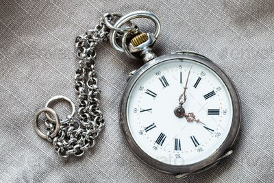 pocket watch with chain on textile background