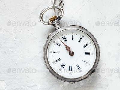 two minutes to twelve on antique watch on concrete