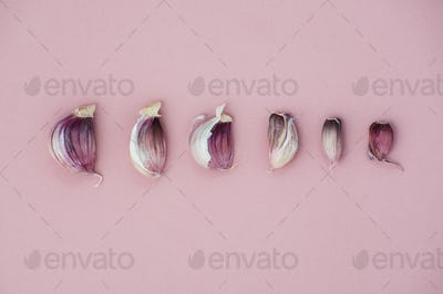 Garlic cloves lined in size on a light pink background.
