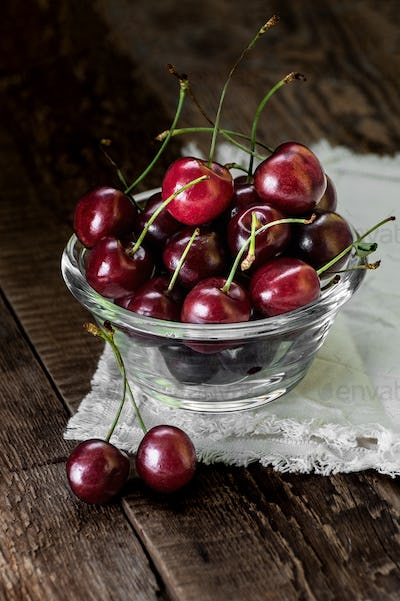 Red sweet cherry in a glass bowl on a dark wooden table close-up
