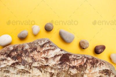 Minimalistic composition of multi-colored sea pebbles on a brigh