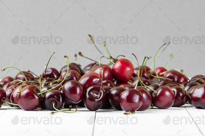 A handful of red cherries on a white wooden table in a crisp pla