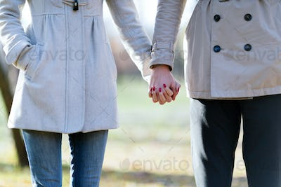 Close-up picture of loving couple holding hands while walking