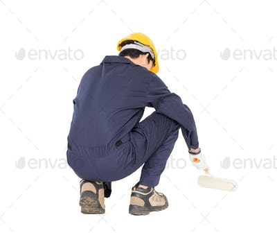 Worker in a uniform using a paint roller-6