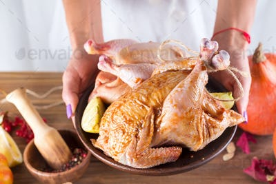 Female hands hold a raw chicken in a plate on the background of a wooden table