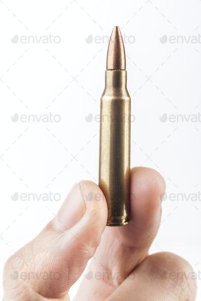 Finger Holding Up Bullet