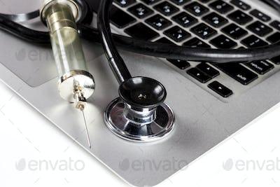 Stethoscope and Syringe on Keyboard