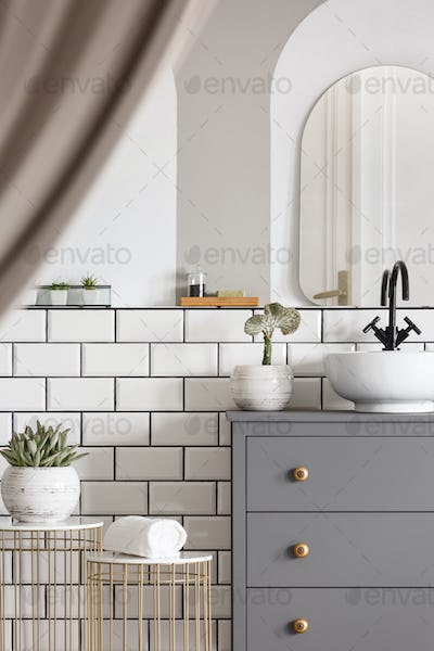 Mirror above grey cabinet with washbasin in bright bathroom inte