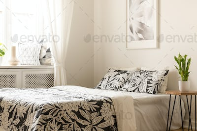 Plant on table next to bed with patterned sheets in bright bedro