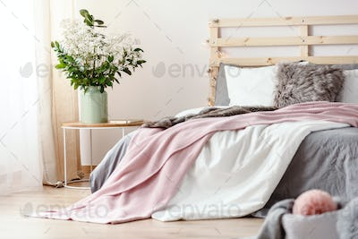 King-size bed with grey sheets and pink blanket standing in brig