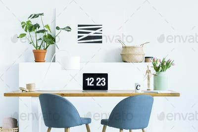 Blue chairs at wooden desk with laptop in white work area with p