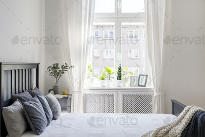 Knit blanket and pillows on bed in white hotel bedroom interior