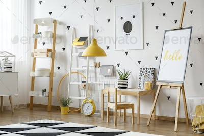Poster on easel and yellow lamp above carpet in bright kid's roo