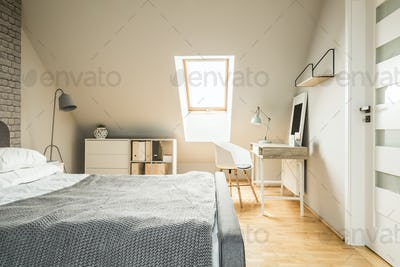Real photo of bright Nordic style attic room interior with woode
