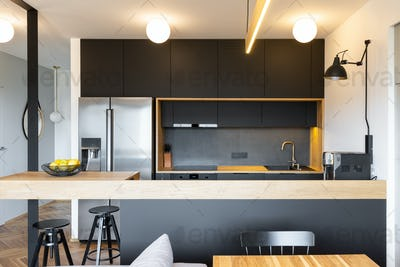 Black wooden furniture and an industrial lamp above a coffee mac