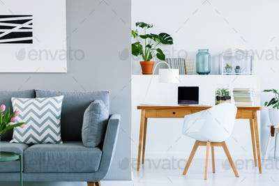 Patterned cushion on grey sofa in scandinavian home office inter