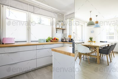 Real photo of bright kitchen interior with windows and dining ta