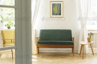 Poster above green wooden sofa in vintage living room interior w