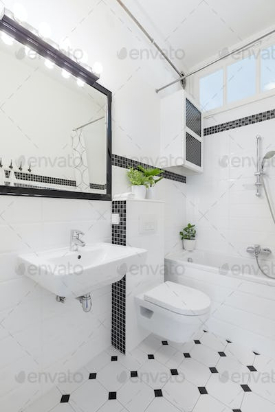 Mirror above washbasin in black and white bathroom interior with