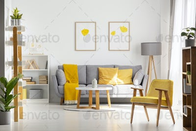 Yellow wooden armchair in bright living room interior with poste