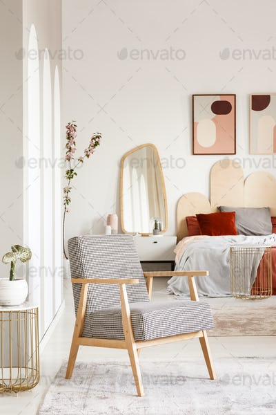 Patterned wooden armchair in pastel bedroom interior with poster