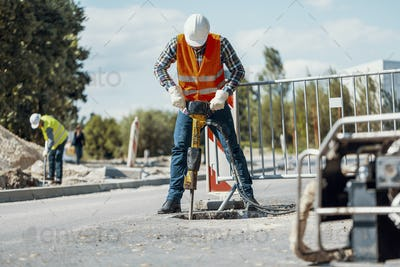 Worker in reflective vest with drill repairing street during roa