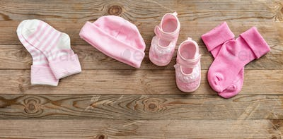 Baby girl shoes and socks on wooden background