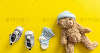 Baby boy shoes and socks on bright yellow background