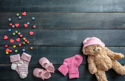 Baby girl shoes and socks on blue wooden background