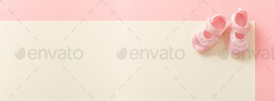 Baby girl shoes on pastel colors background, banner