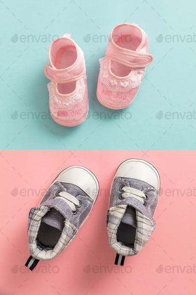 Baby boy and girl shoes on pastel colors background