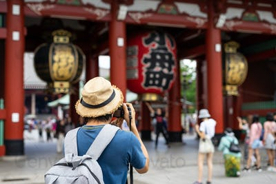 Young traveler taking photo of Sensoji temple in asakusa, Tokyo, Japan