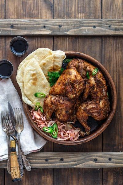 Tandoori chicken. Half of tandoori chicken served with lime slices and cilantro. Copy space