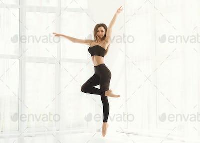 Beautiful graceful woman dancing in white studio