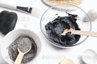 Preparing cosmetic black mud mask in glass bowl