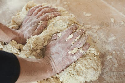 Male hands kneading dough on wooden table