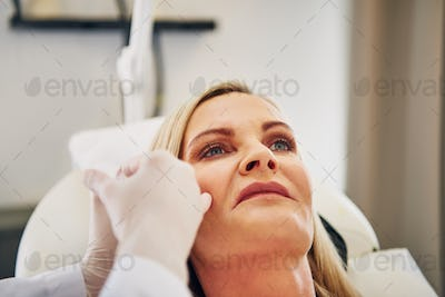Mature woman getting botox injections at a beauty clinic