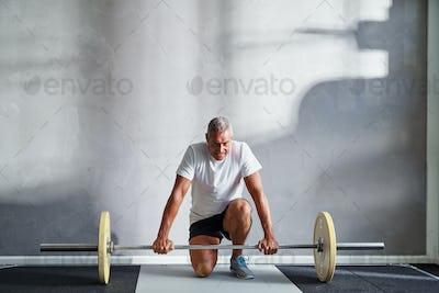 Senior man preparing to lift weights at the gym