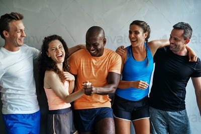 Diverse group of friends laughing together at the gym
