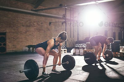 Sportive man and woman deadlifting in gym