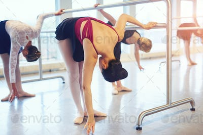 Ballet dancers stretching and bending in class