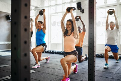 Smiling young woman working out with friends at the gym