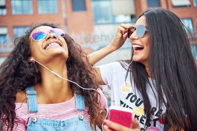 Young girlfriends sitting outside together listening to music on earphones