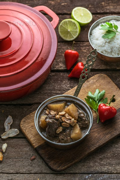 Massaman Beef Curry Served In copper pan, wooden background